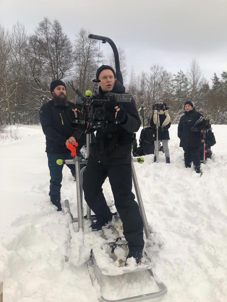 Grip Aki Laulajainen kuvaajan takana lumen keskellä, kaikilla toppavaatteet päällä.