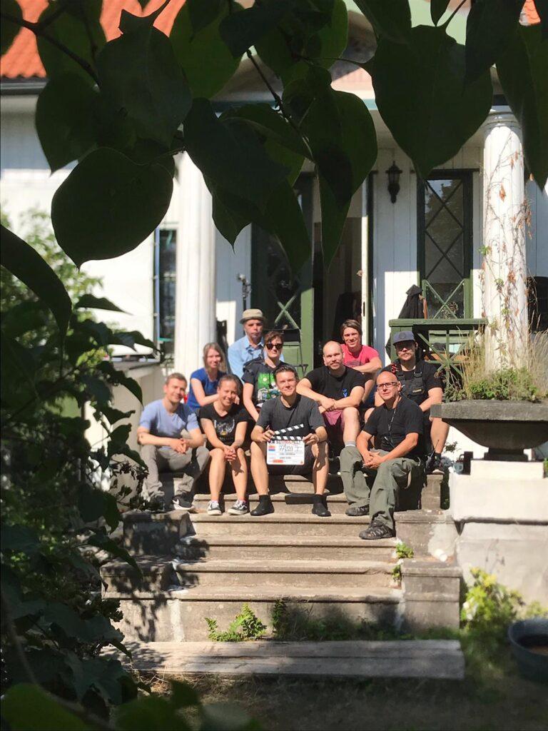 Seurapeli-elokuvan kamera- valo- ja gripryhmää istumassa portailla