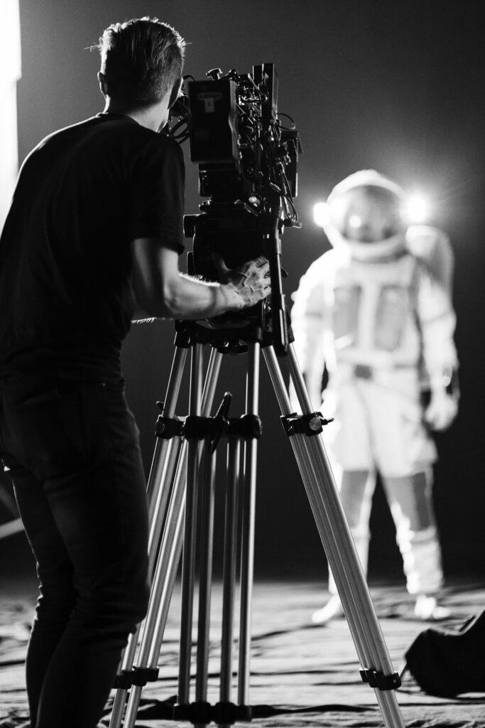 Jarmo kameran kanssa kuvaamassa astronauttipukuista hahmoa